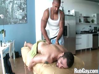 Tired homo rugby player receives a priceless relaxing massage on his back and wazoo from a masseur fellow