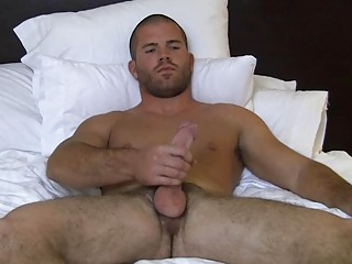 Muscled bald homosexual hunk wanks his big hard knob on couch