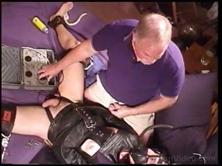 Guy in a leather straitjacket is fondled and teased by old fellow