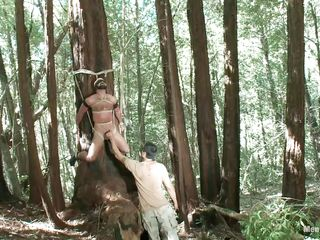 this chab has done something to offend this chap and this chab is not about to let this golden opportunity to extract his revenge in the almost any painful way possible. this chab has bound him to a tree and this chab is hanging by the ropes that are cutting him into it as this chab plays and teases his ramrod at his own leisure as a prelude.