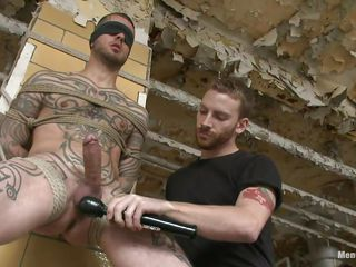 Tattooed dude stays next to a wall all bound up. Some other dude takes pics with him, then his boyfriend starts licking and engulfing his very hard cock. His hairless balls are too being licked and then a sex-toy comes to play with his head and balls. That dude is feeding himself and the other with pre-cum. Check it out!