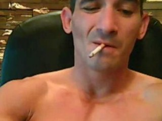 Tatooed tough man smokes while strokes his cock